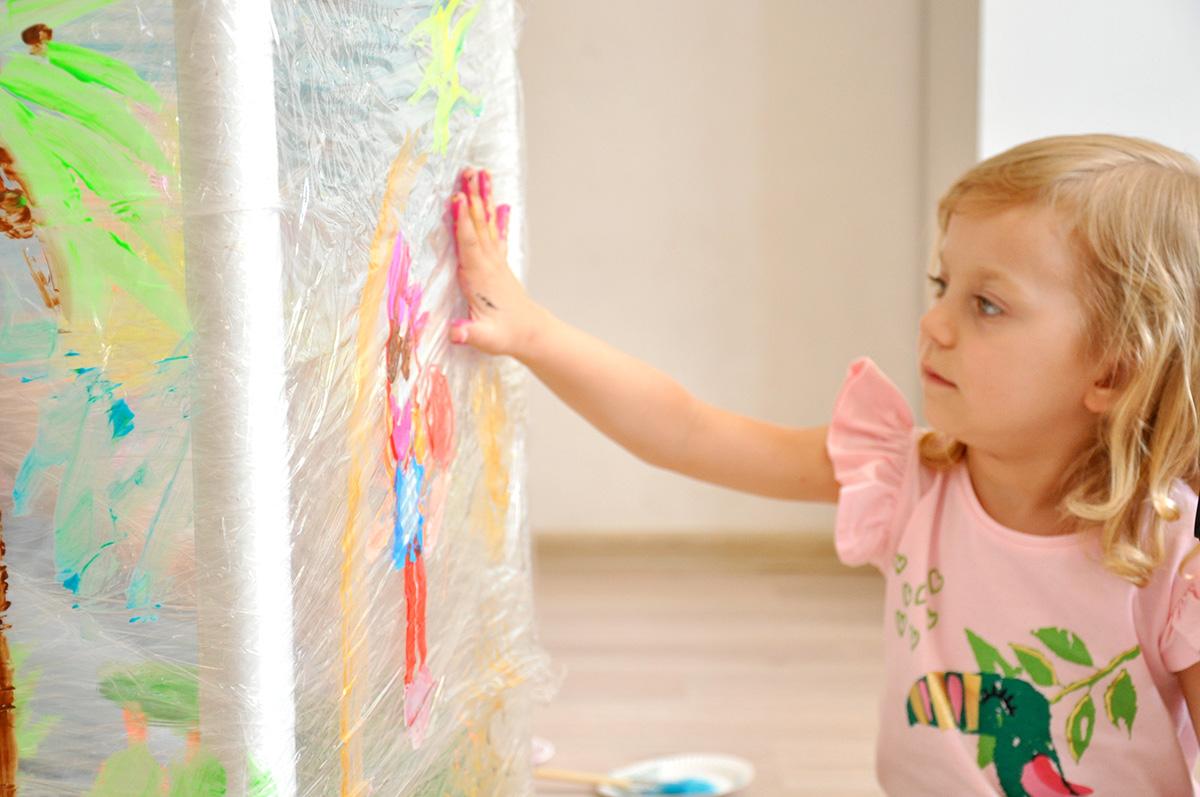 Dziecko malujące dłonią na folii spożywczej.