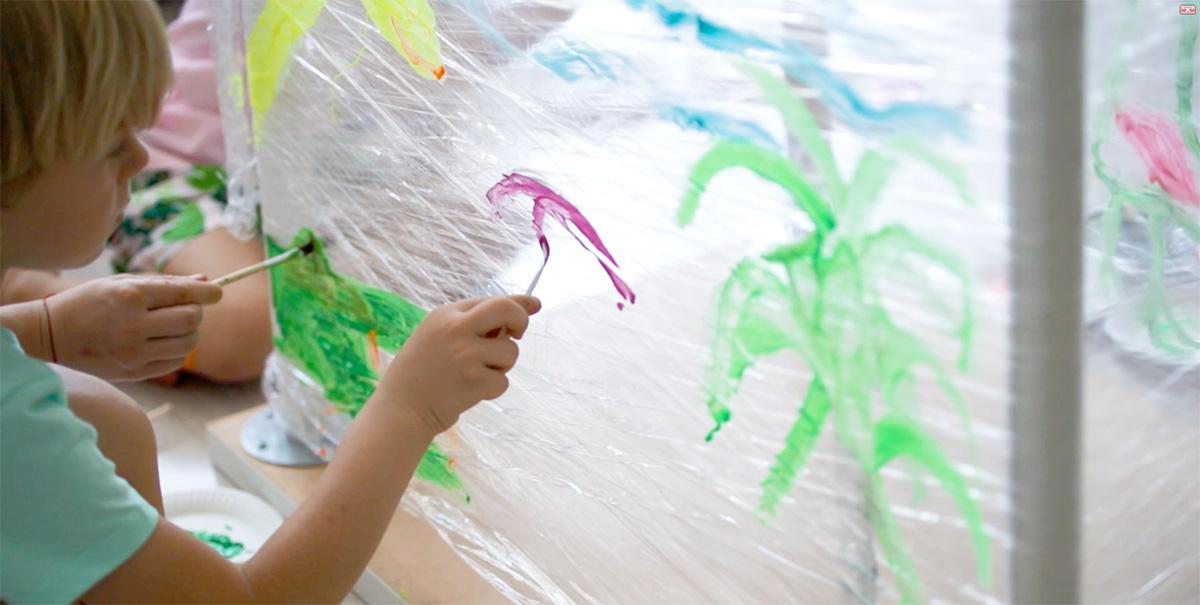 Chłopiec malujący fioletową farbą po rozciągniętej folii spożywczej.