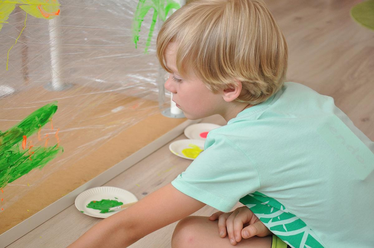Chłopiec sięgający po farby do malowania na rozciągniętej dla folii stretch.