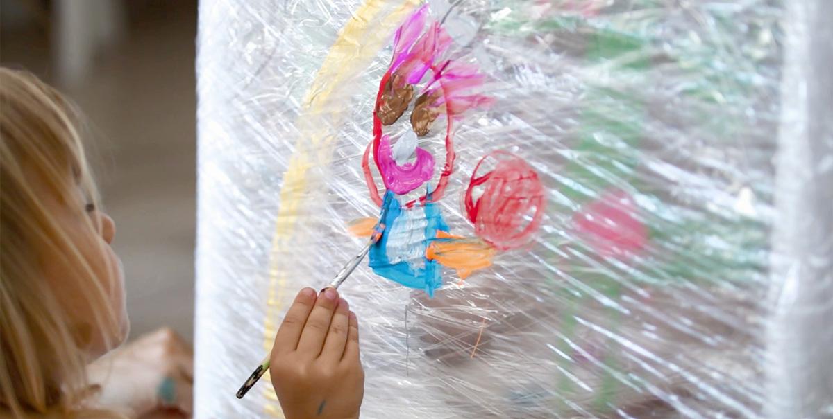 Dziewczynka malująca kolorowego ludka na rozciągniętej folii spożywczej.