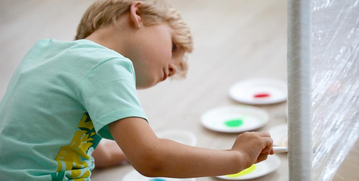 Chłopiec malujący pędzelkiem po rozciągniętej folii spożywczej.
