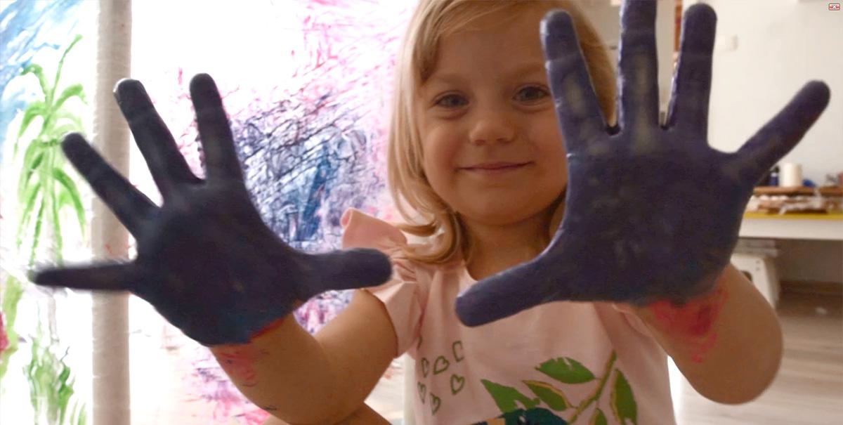 Dziewczynka prezentująca pomalowane fioletowe dłonie po zabawie farbami.