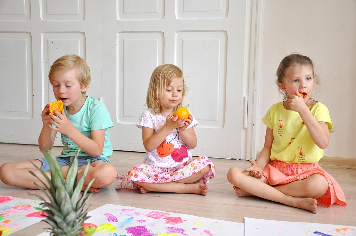 Dzieci siedzące na podłodze, jedzące pomarańcze podczas zabawy ze stemplami z warzyw i owoców.