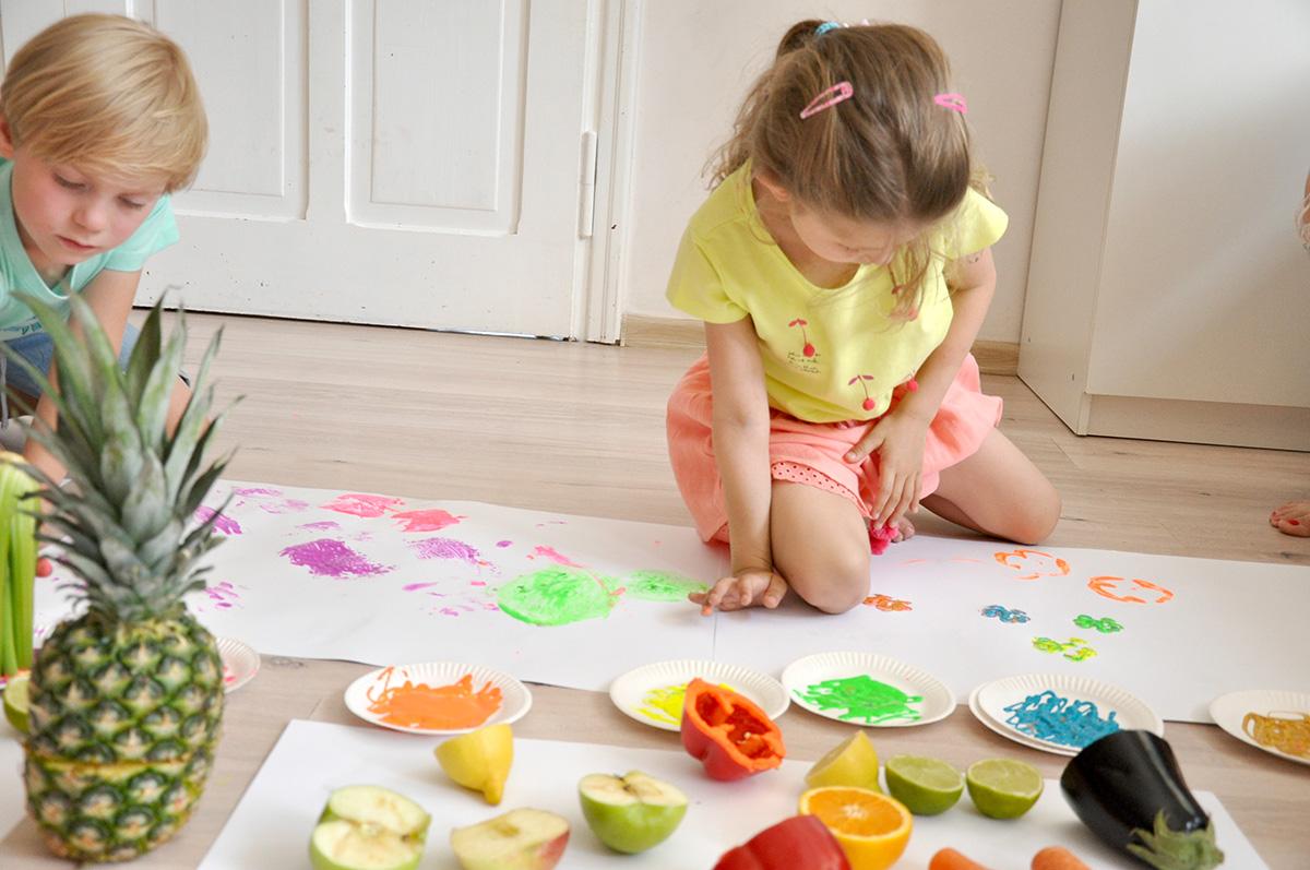 Dzieci odciskające kolorowe stemple z warzyw i owoców na papierze.
