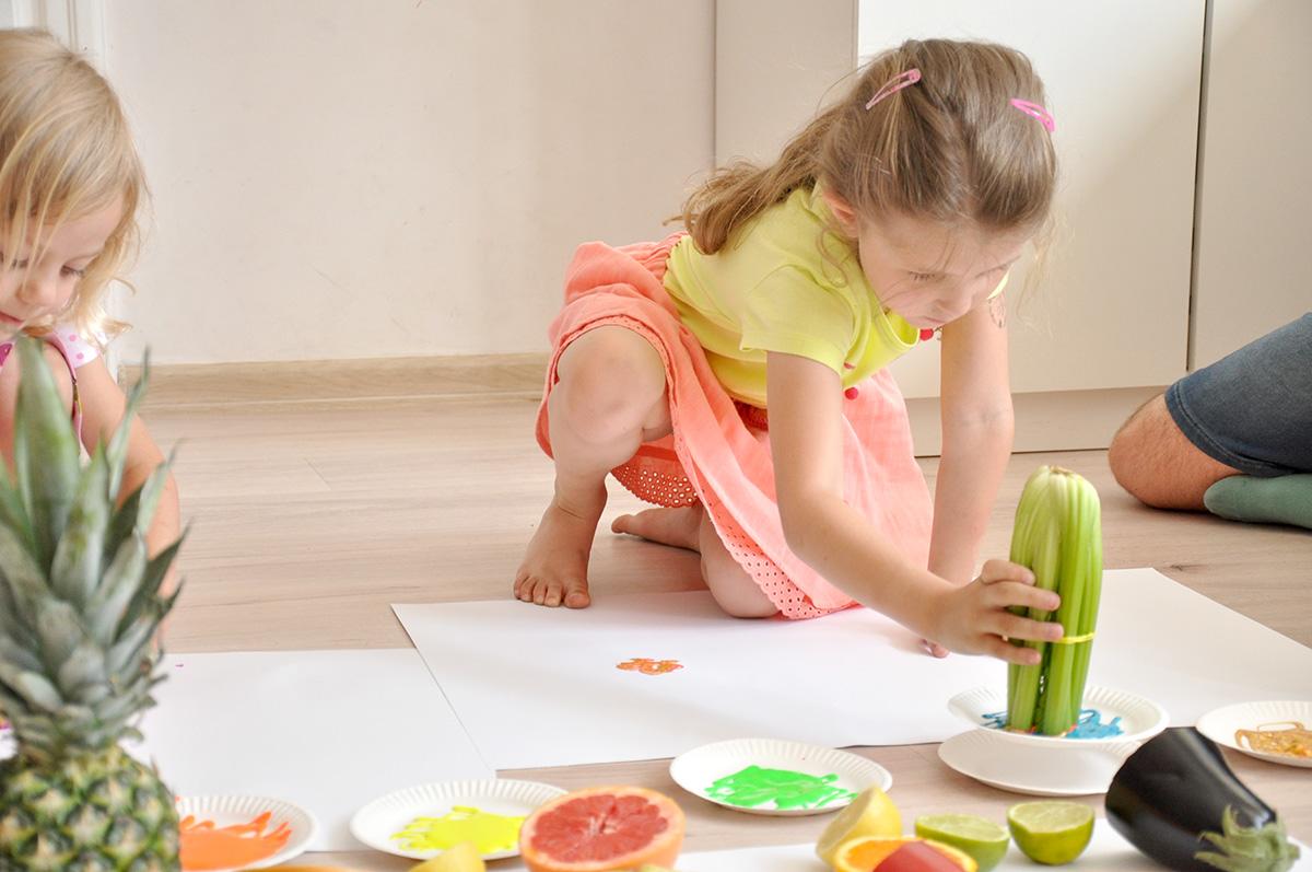 Dziewczynka używająca selera naciowego jako stempla na papierze.