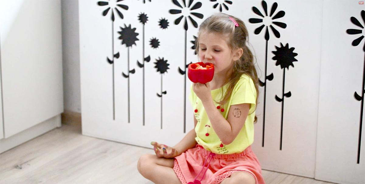 Dziewczynka siedząca na podłodze jedząca paprykę podczas zabawy z warzywami i farbami.