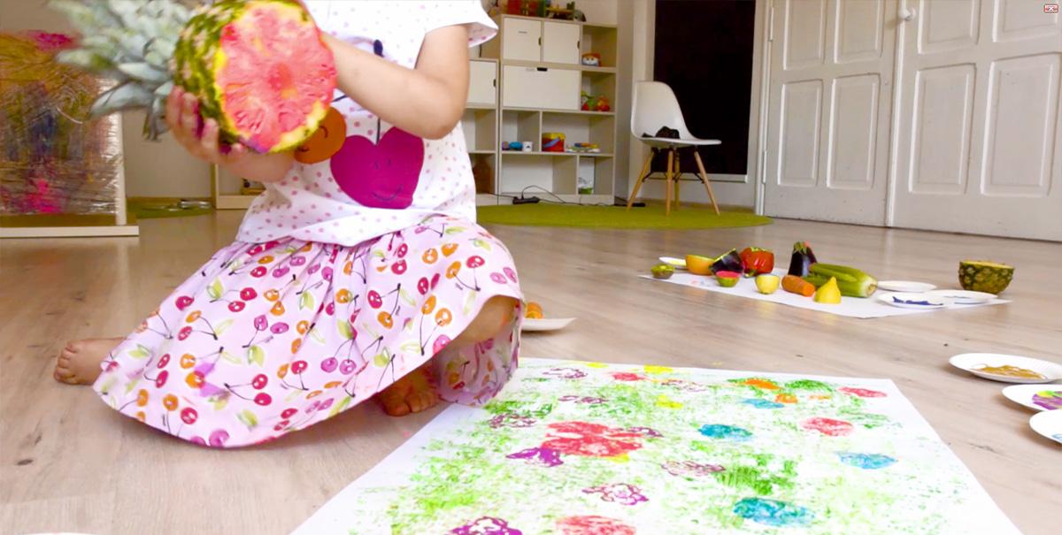 Dziewczynka odciskająca kolorowy stempel z ananasa na papierze.