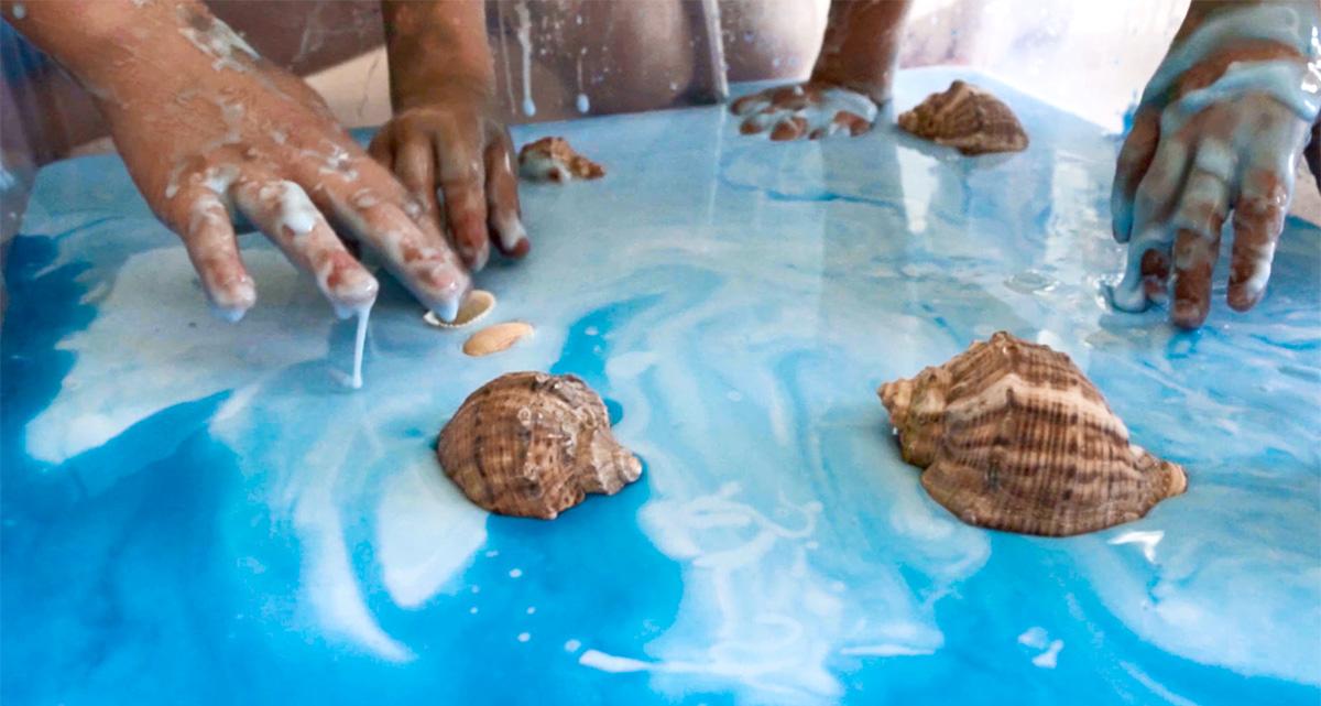 Muszelki wrzucone do miski z niebieską cieczą nienewtonowską.