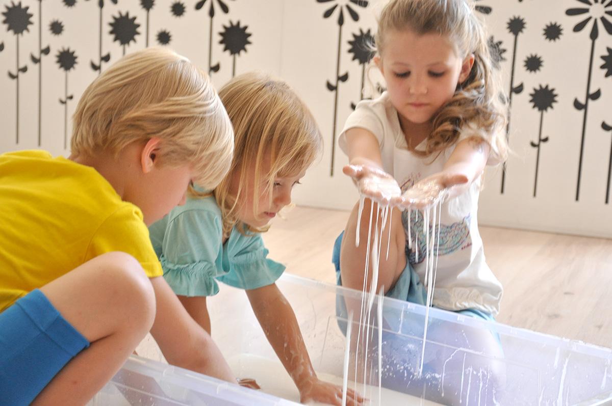 Dzieci bawią się zmieniającą stan cieczą nienewtonowską.