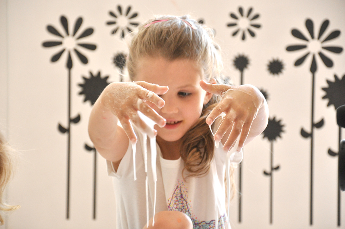Dziewczynka obserwuje jak ciecz nienewtonowska przelewa jej się przez palce.