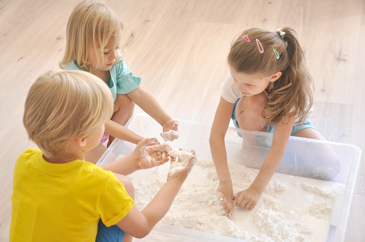 Dzieci ugniatają wodę z mąką w dużym plastikowym pojemniku.