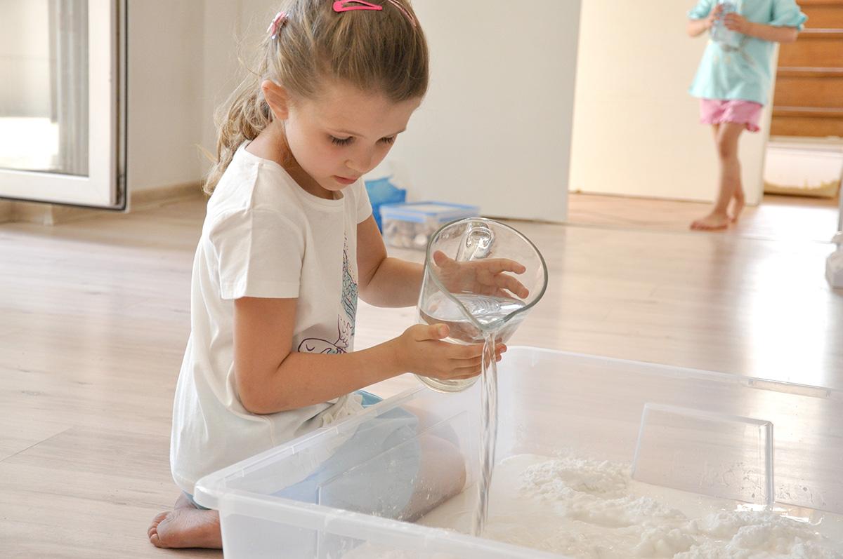 Dziewczynka nalewa wody do pojemnika z mąką ziemniaczaną.
