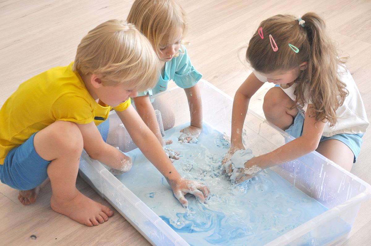 Dzieci bawią się zabarwioną na niebiesko cieczą nienewtonowską.