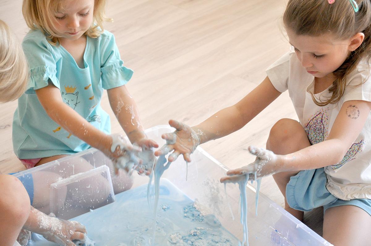 Dziewczynki obserwują jak mieszkanka wody i mąki przelewa im się przez dłonie.
