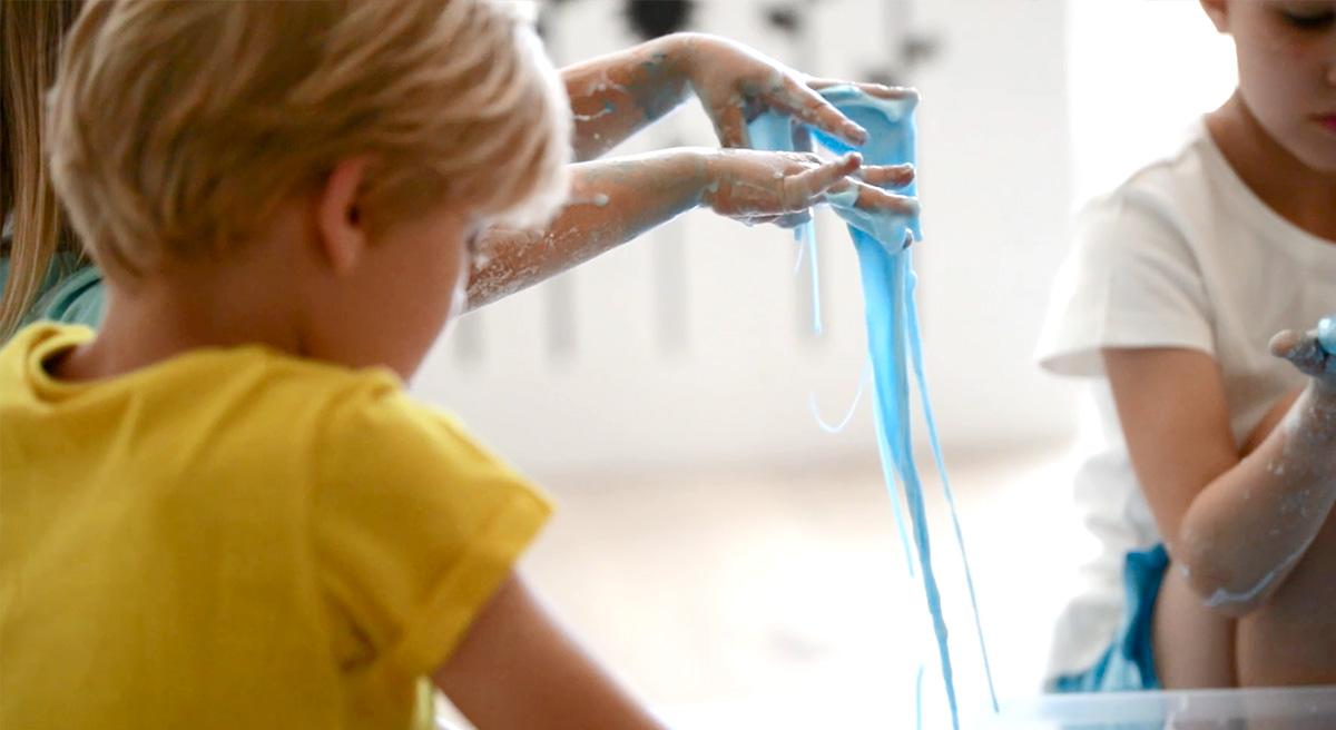 Dziecko pokazuje jak niebieska ciecz nienewtonowska przelewa jej się przez palce.