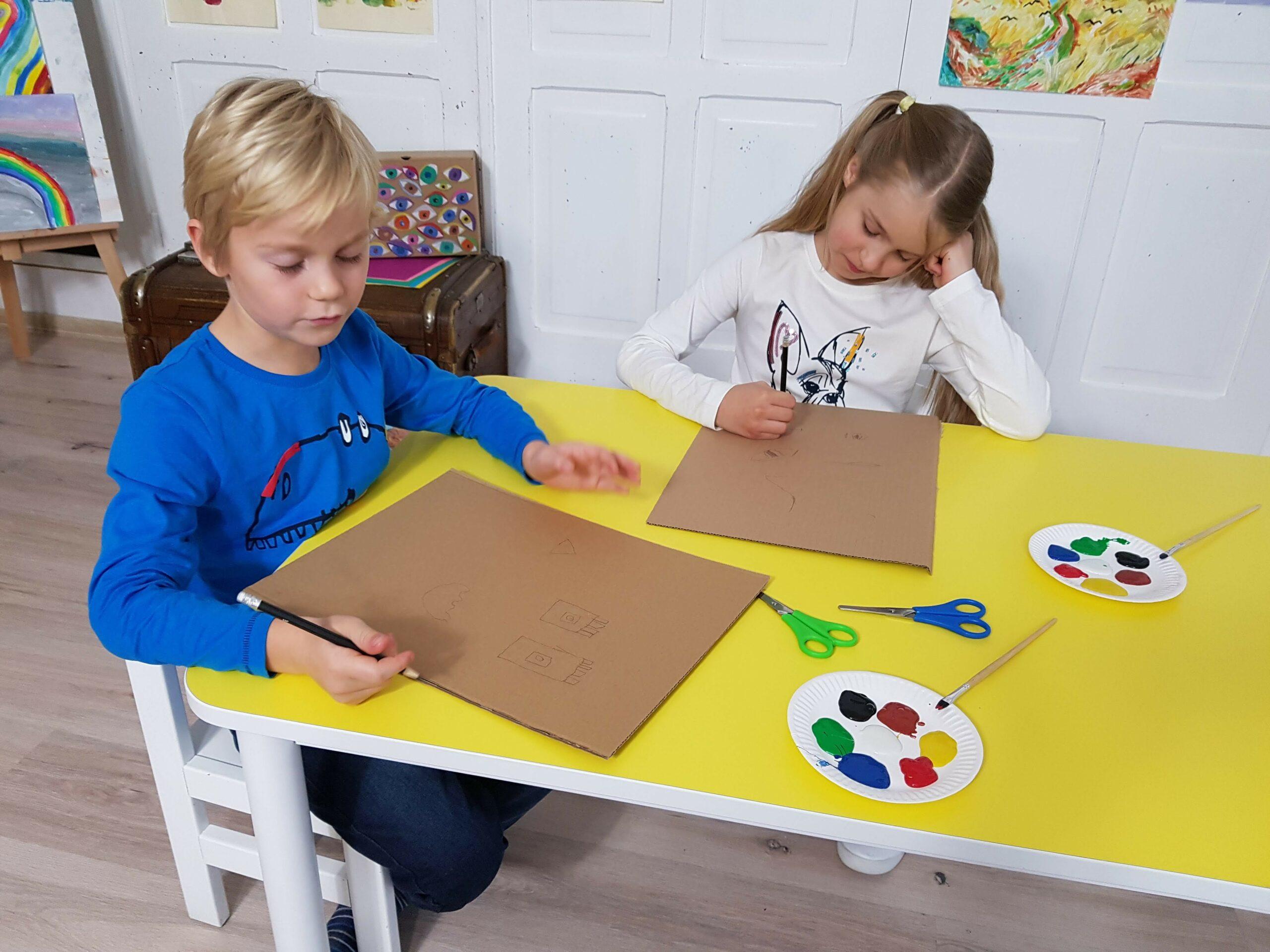 Dzieci malujące geometryczne kształty na kartonie.