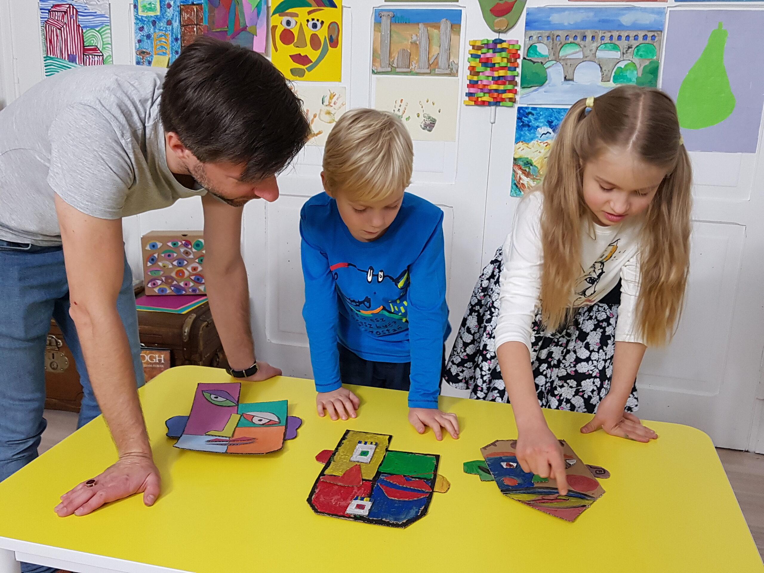 Dzieci omawiają swoje kubistyczne portrety z pedagogiem.