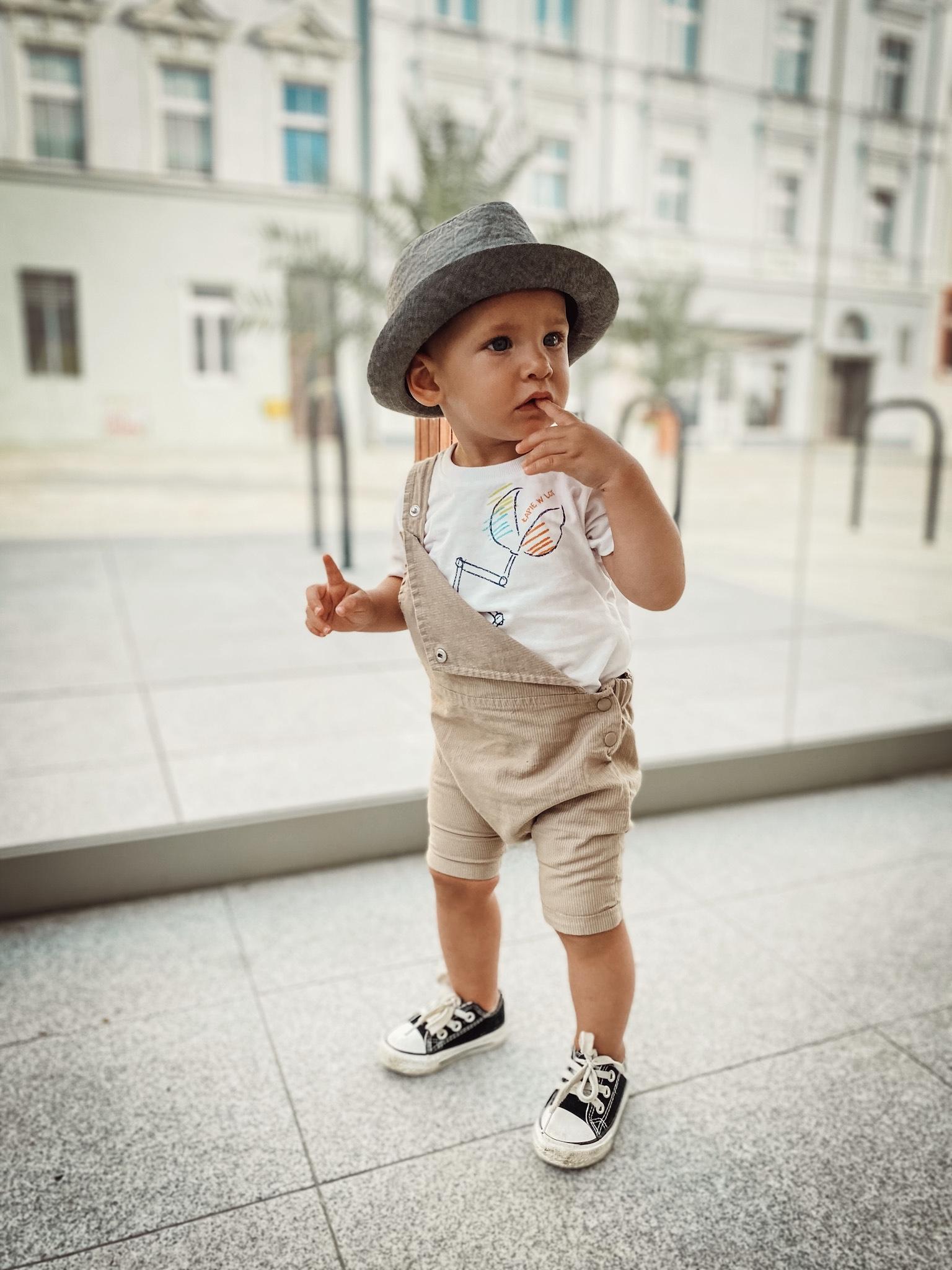 Mały chłopiec w jasnych ogrodniczkach i kapeluszu na głowie.