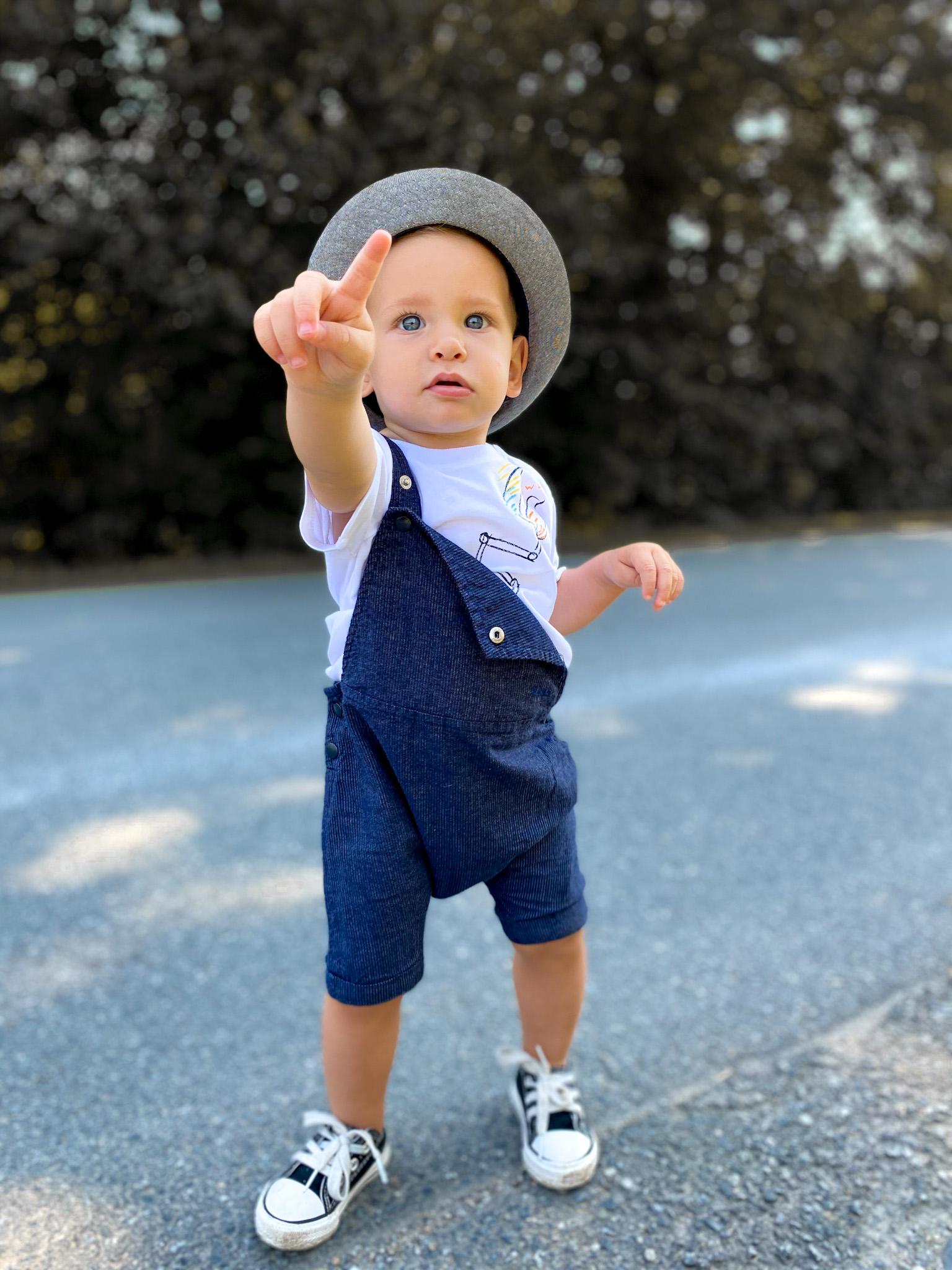 Mały chłopiec w niebieskich ogrodniczkach i kapeluszu na głowie.