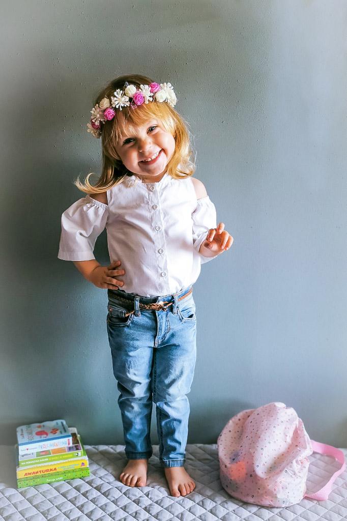 Mała dziewczynka w białej koszuli, jeansach i z wiankiem na głowie.