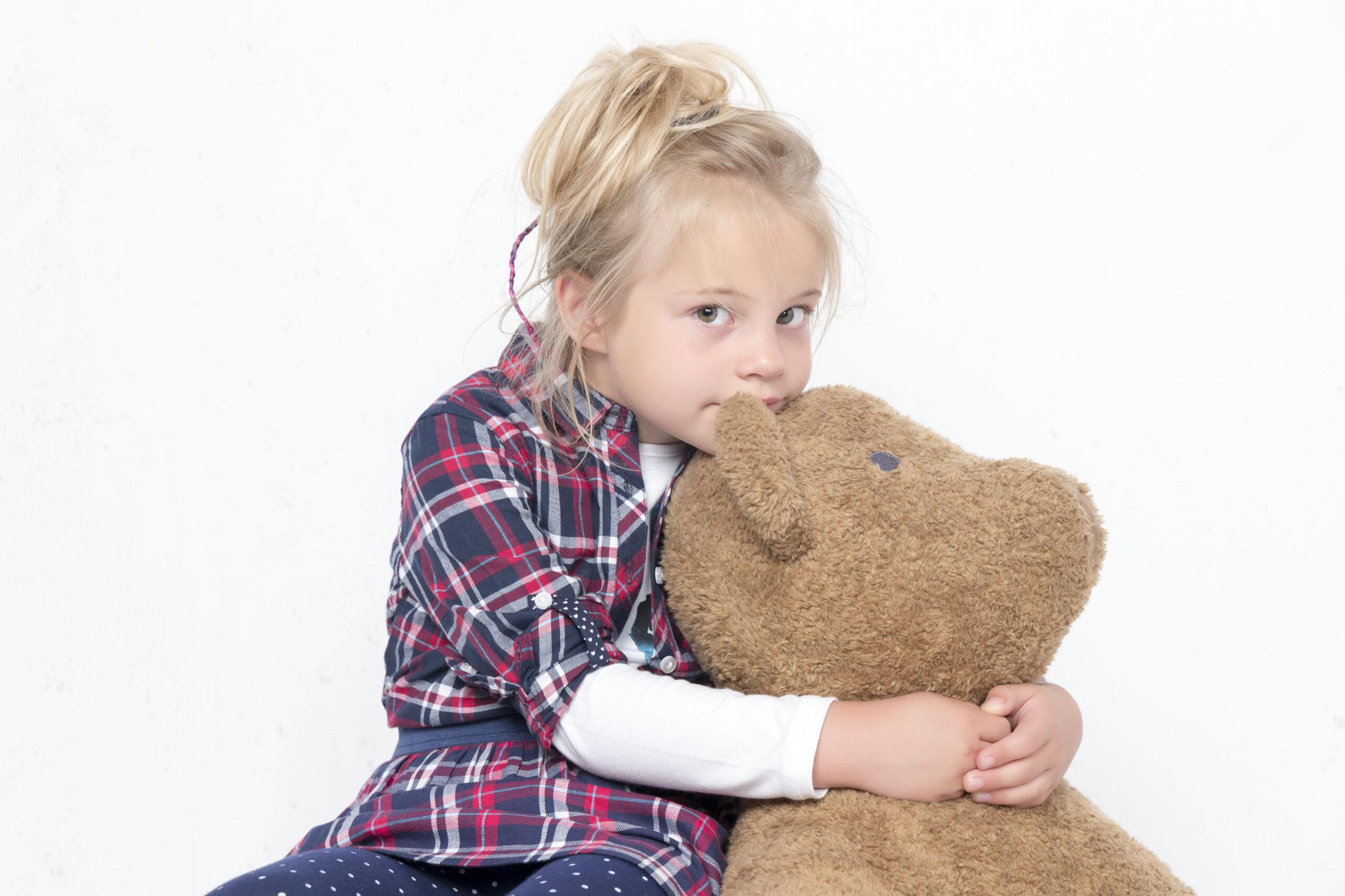 Mała dziewczynka przytulająca dużego misia.