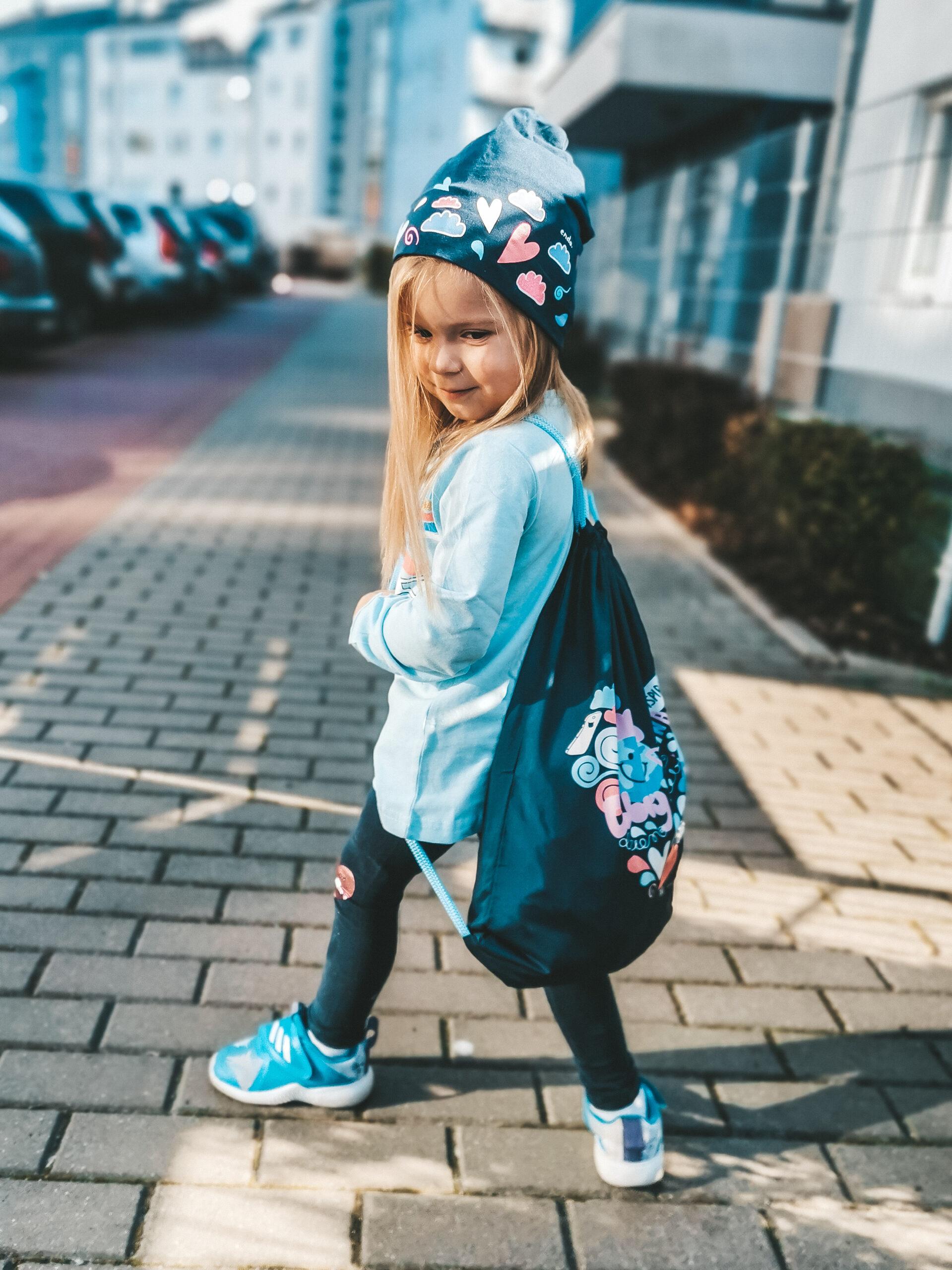 Mała dziewczynka w miejskiej stylizacji złożonej z czapki, worka-plecaka, legginsów i bluzki z długim rękawem.