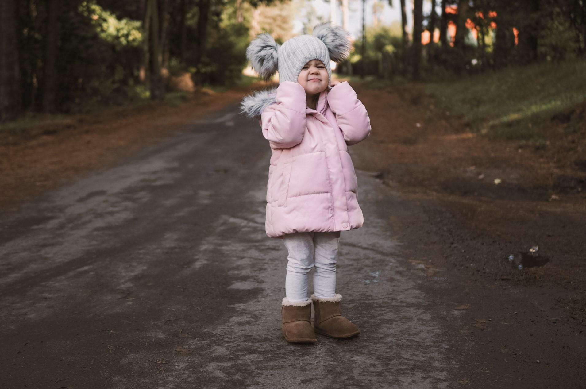 Mała dziewczynka ubrana w różową kurtkę, naciągająca czapkę na uszy.