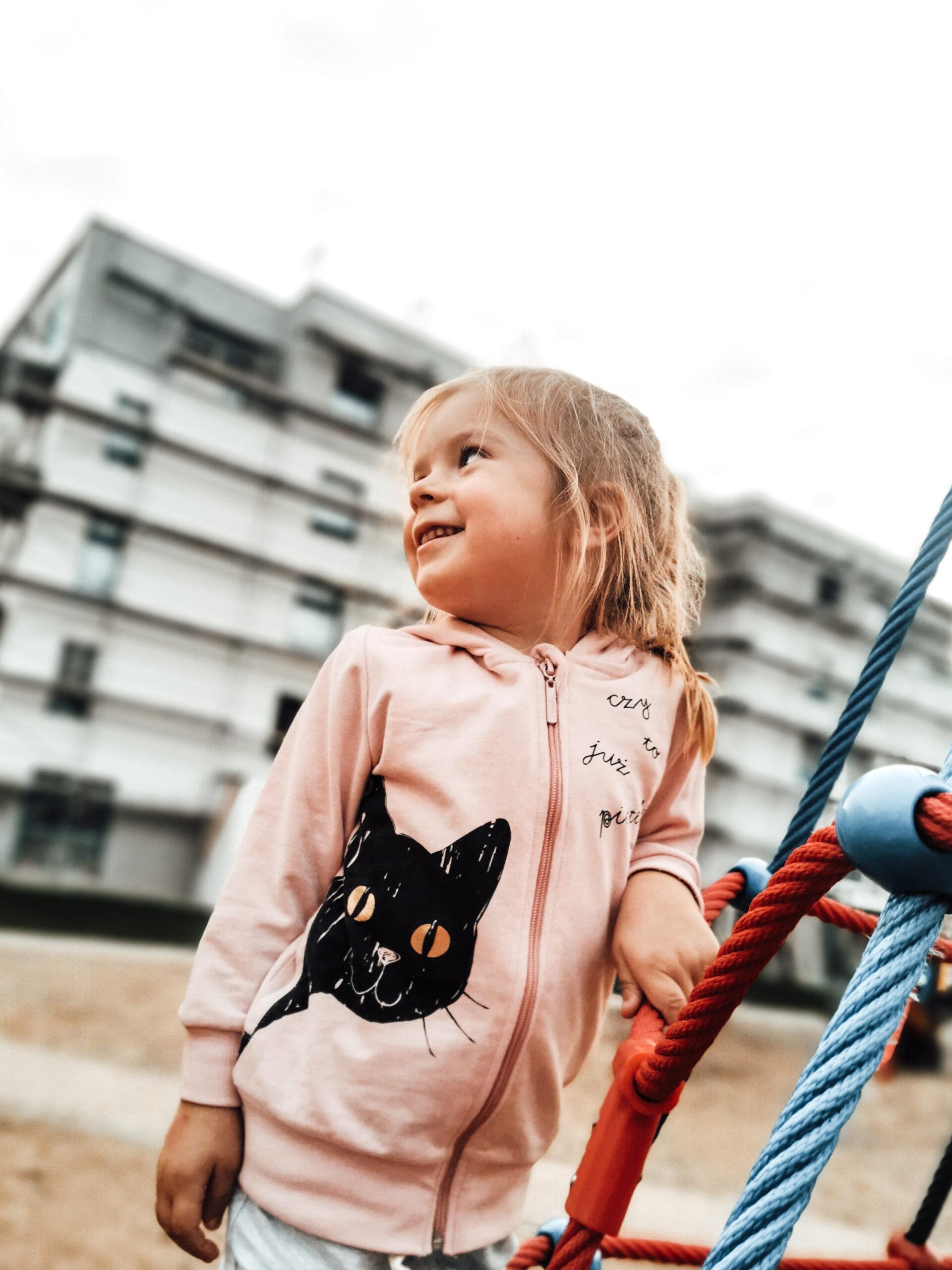 Mała dziewczynka w różowej bluzie na placu zabaw.