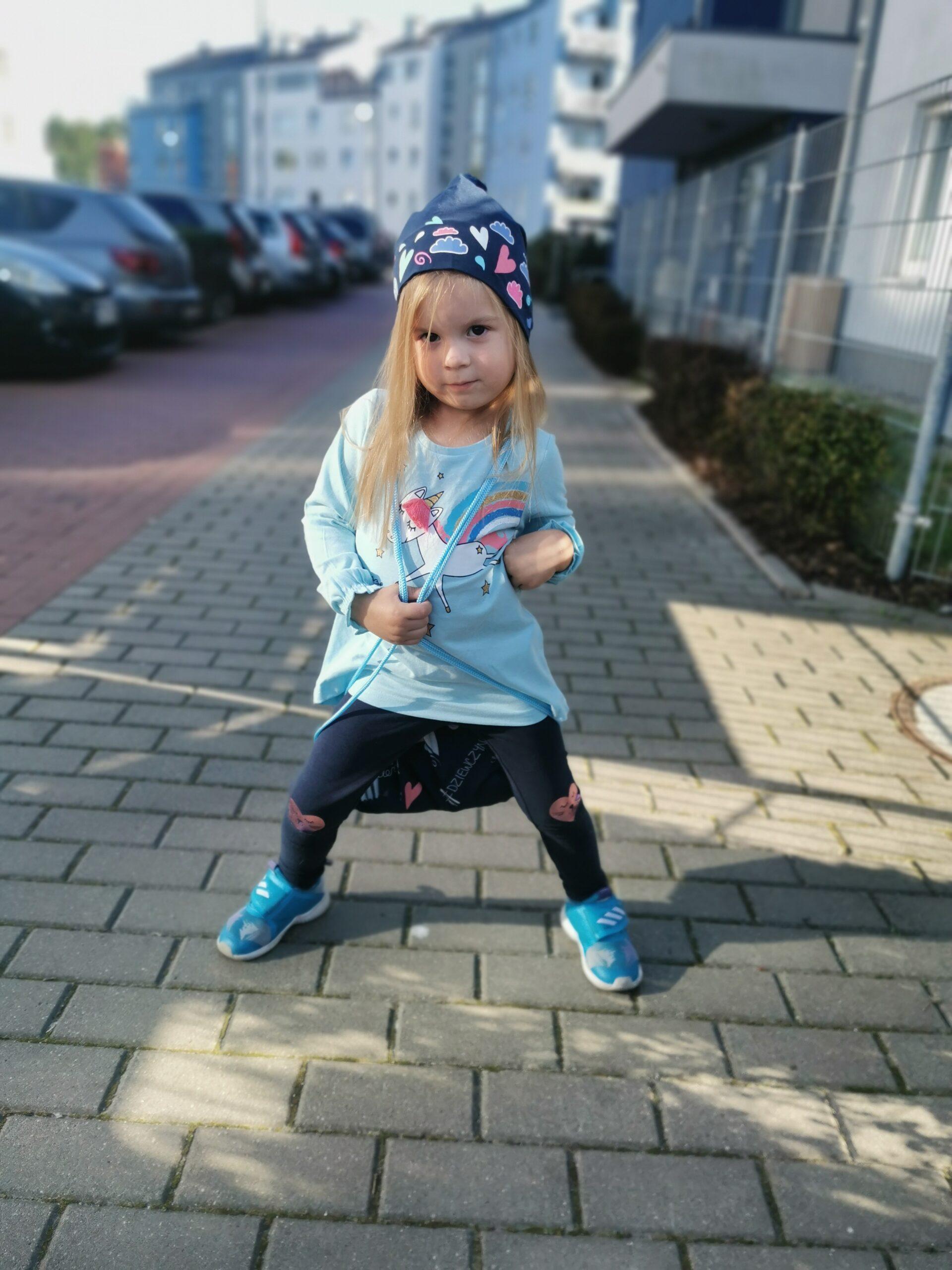 Mała dziewczynka w granatowej czapce pozująca do zdjęcia na chodniku.