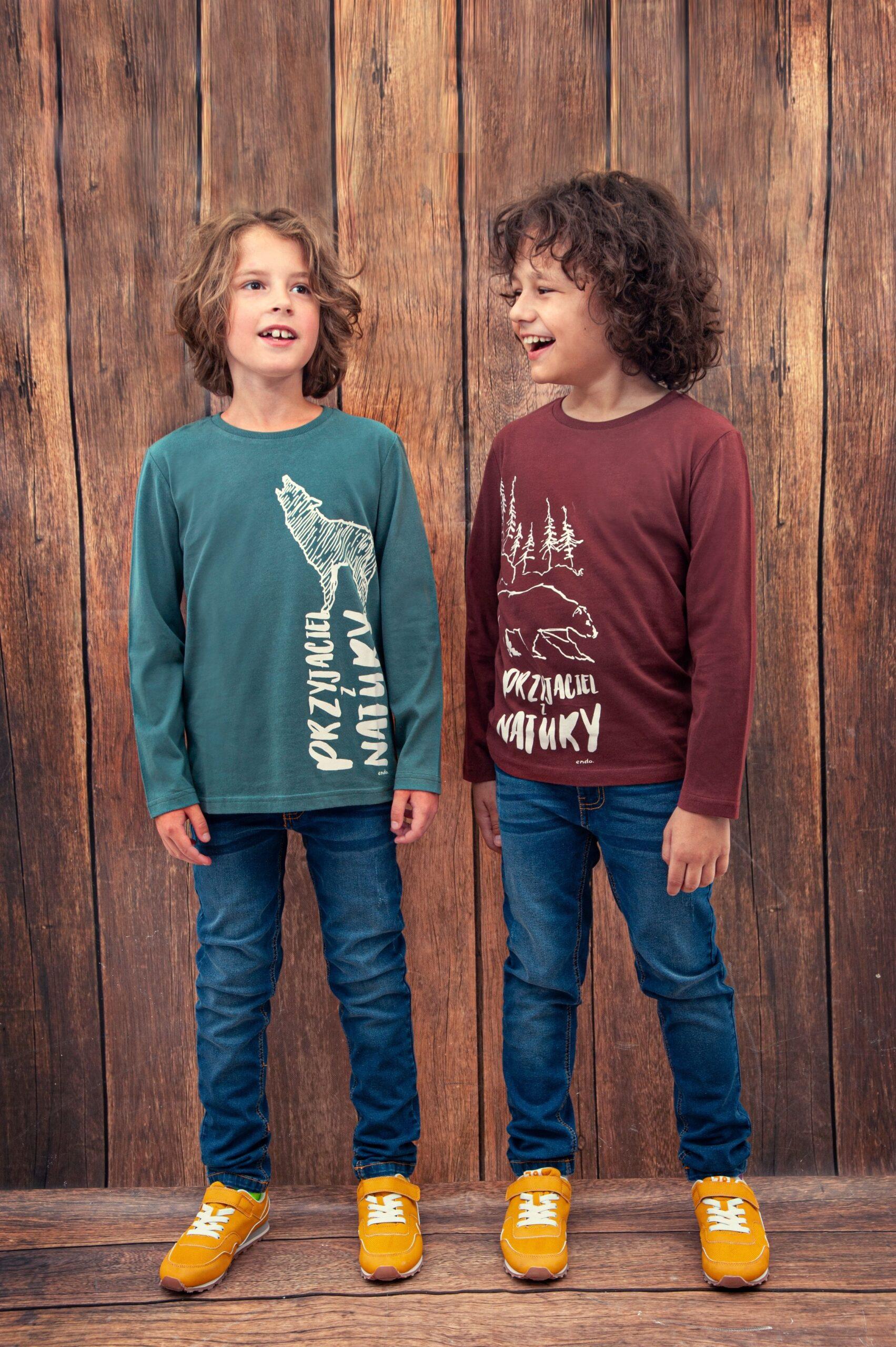 Dwaj chłopcy stojący na tle drewnianej ściany, śmiejący się do siebie.