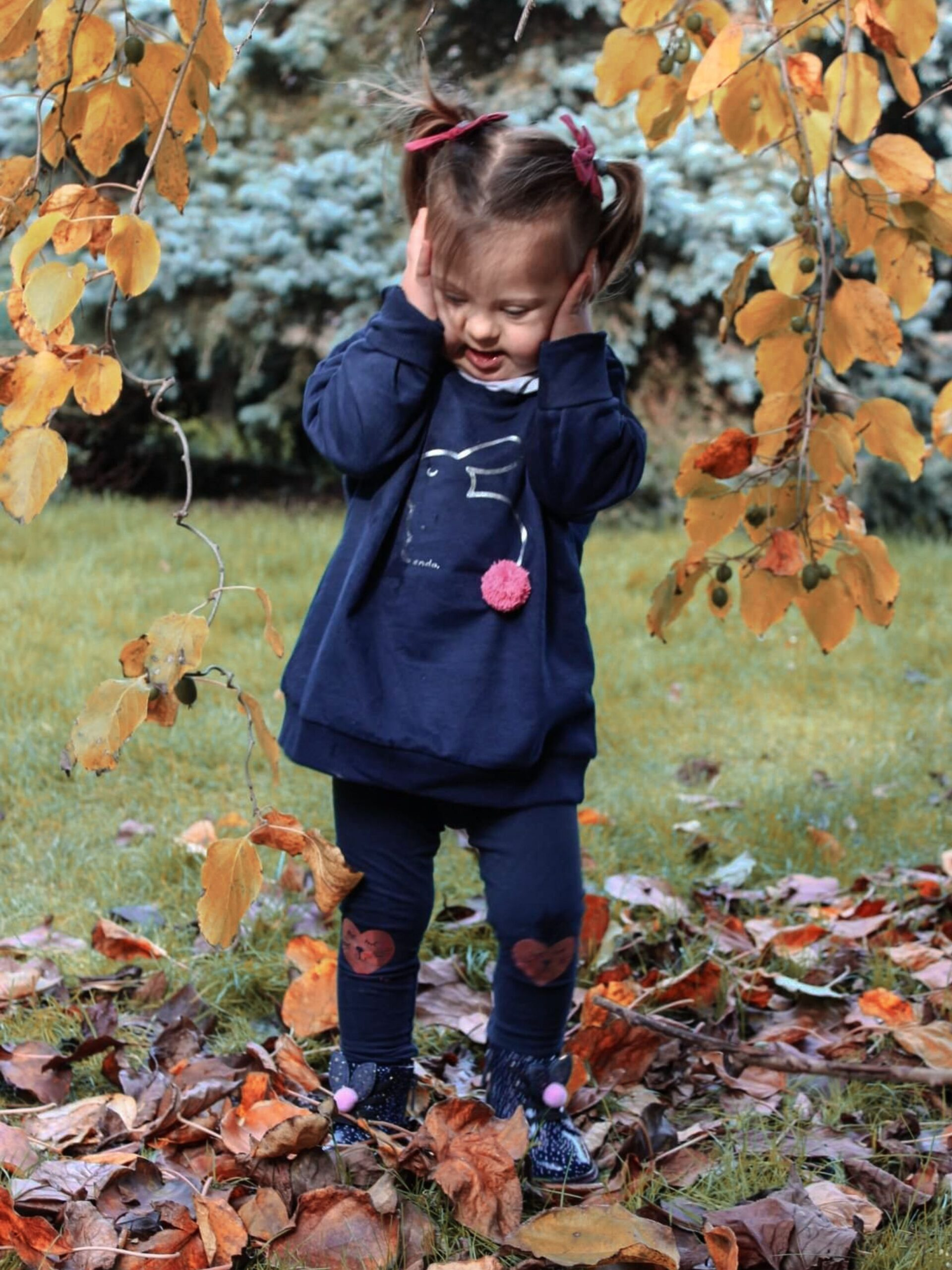 Mała dziewczynka trzymająca się za głowę, stojąca wśród liści w parku.