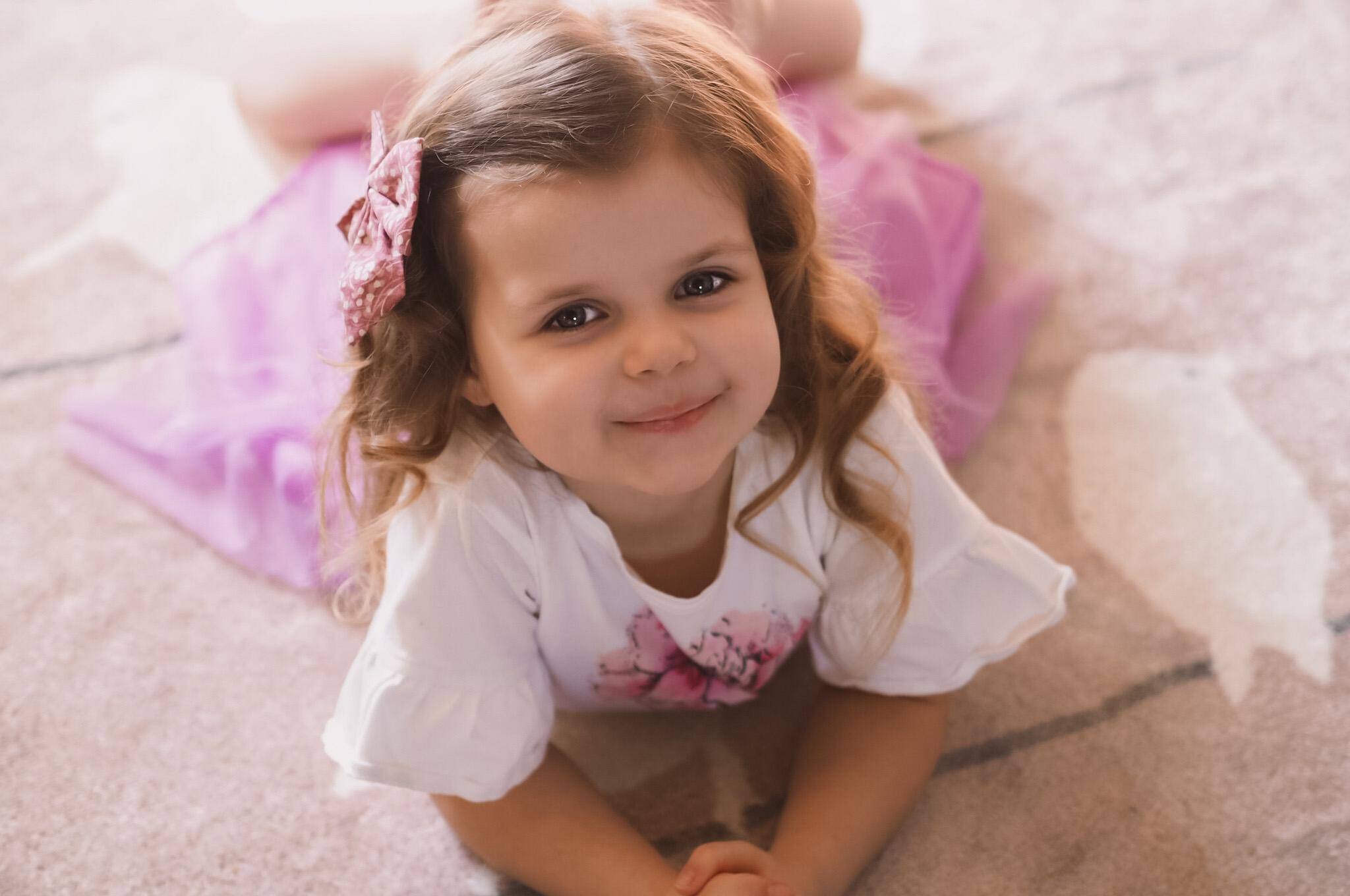 Mała dziewczynka w sukience z tiulem, leżąca na podłodze i uśmiechająca się do aparatu.