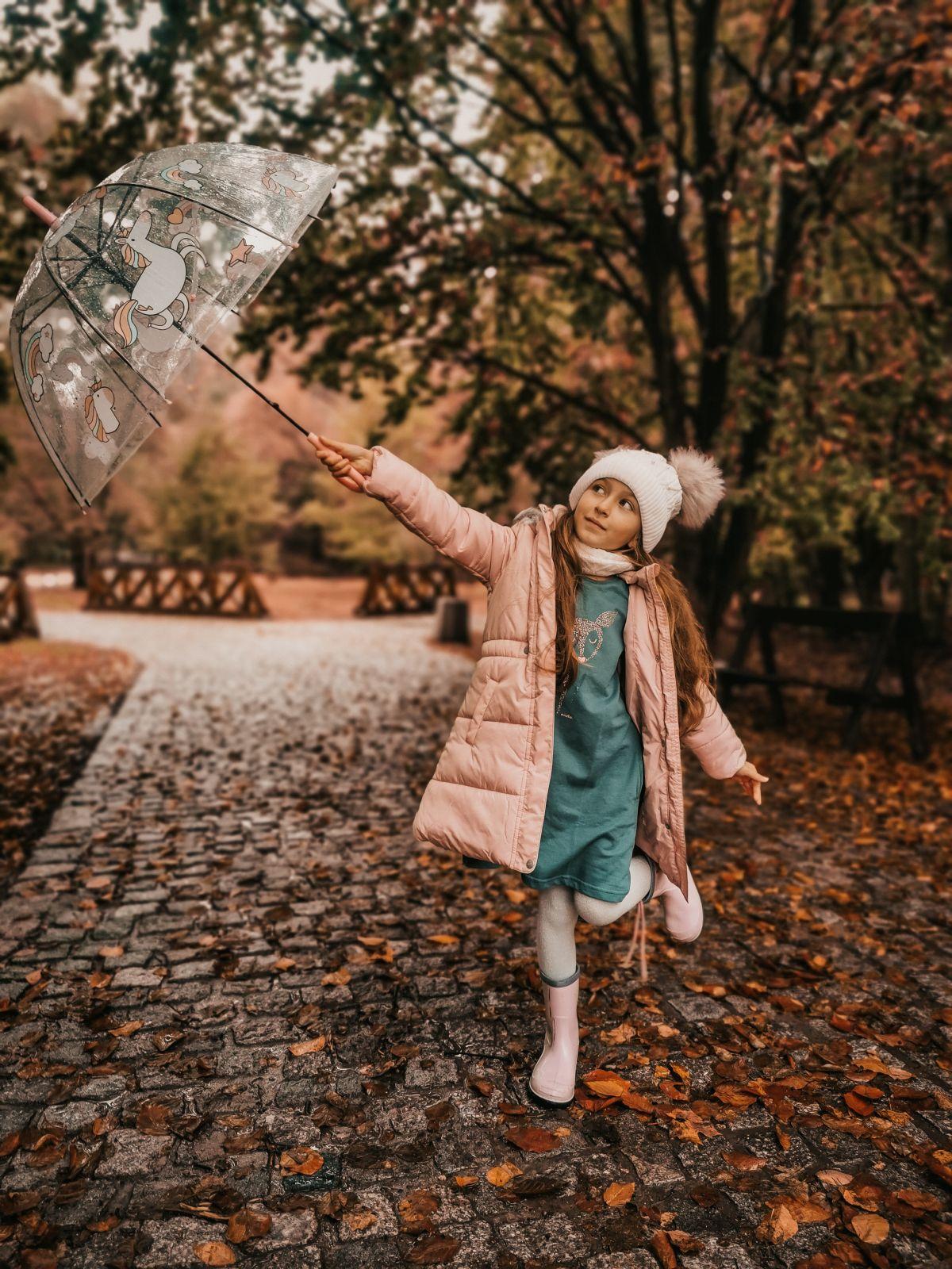Dziewczynka pozująca do zdjęcia w jesiennym parku, z parasolem w ręku.
