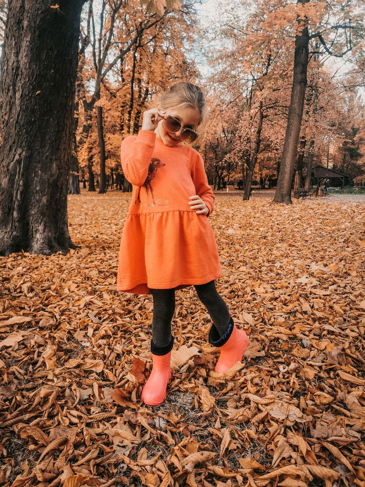 Dziewczynka w pomarańczowej sukience pozująca do zdjęcia w jesiennym parku.