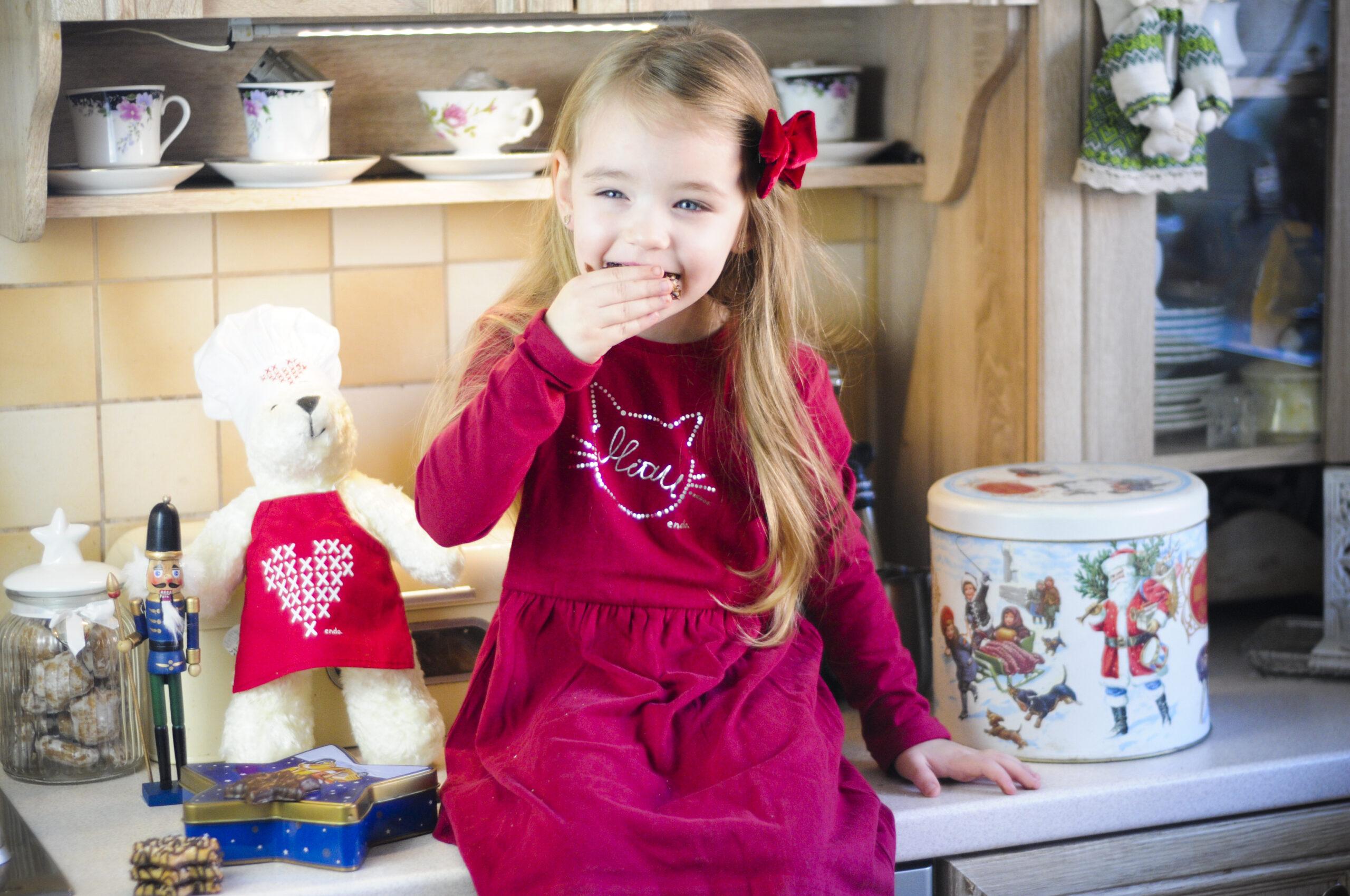 Mała dziewczynka w czerwonej sukience jedząca piernik świąteczny na blacie w kuchni.