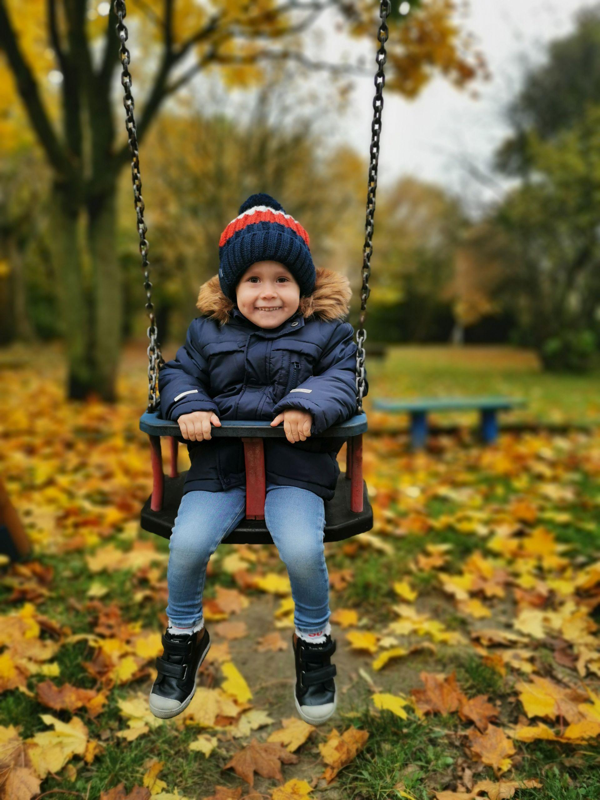 Chłopiec ubrany w kurtkę na huśtawce w jesiennej scenerii.