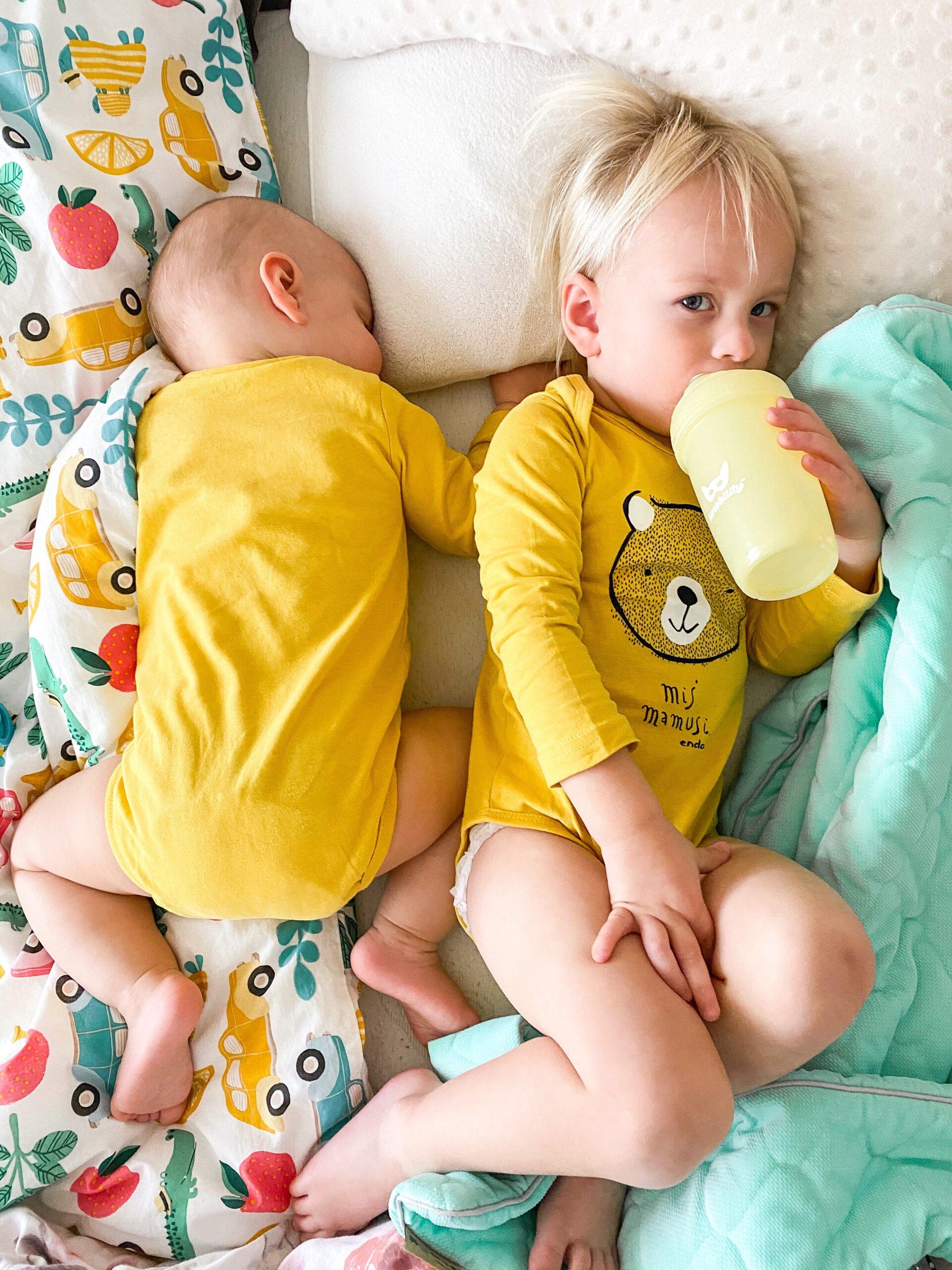 Mali chłopcy śpiący w żółtych body.