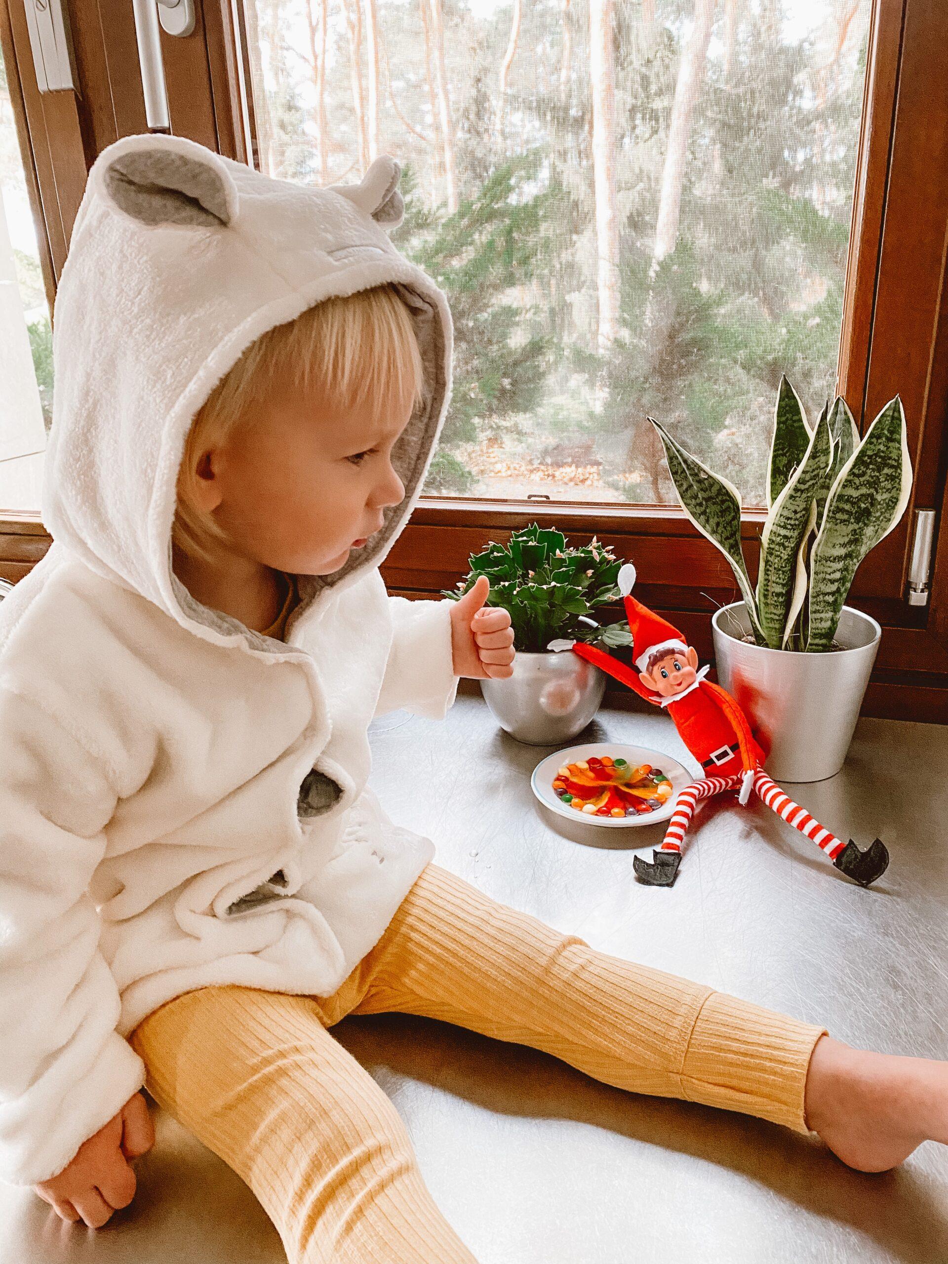 Mały chłopiec ubrany w biały polarowy kubraczek.