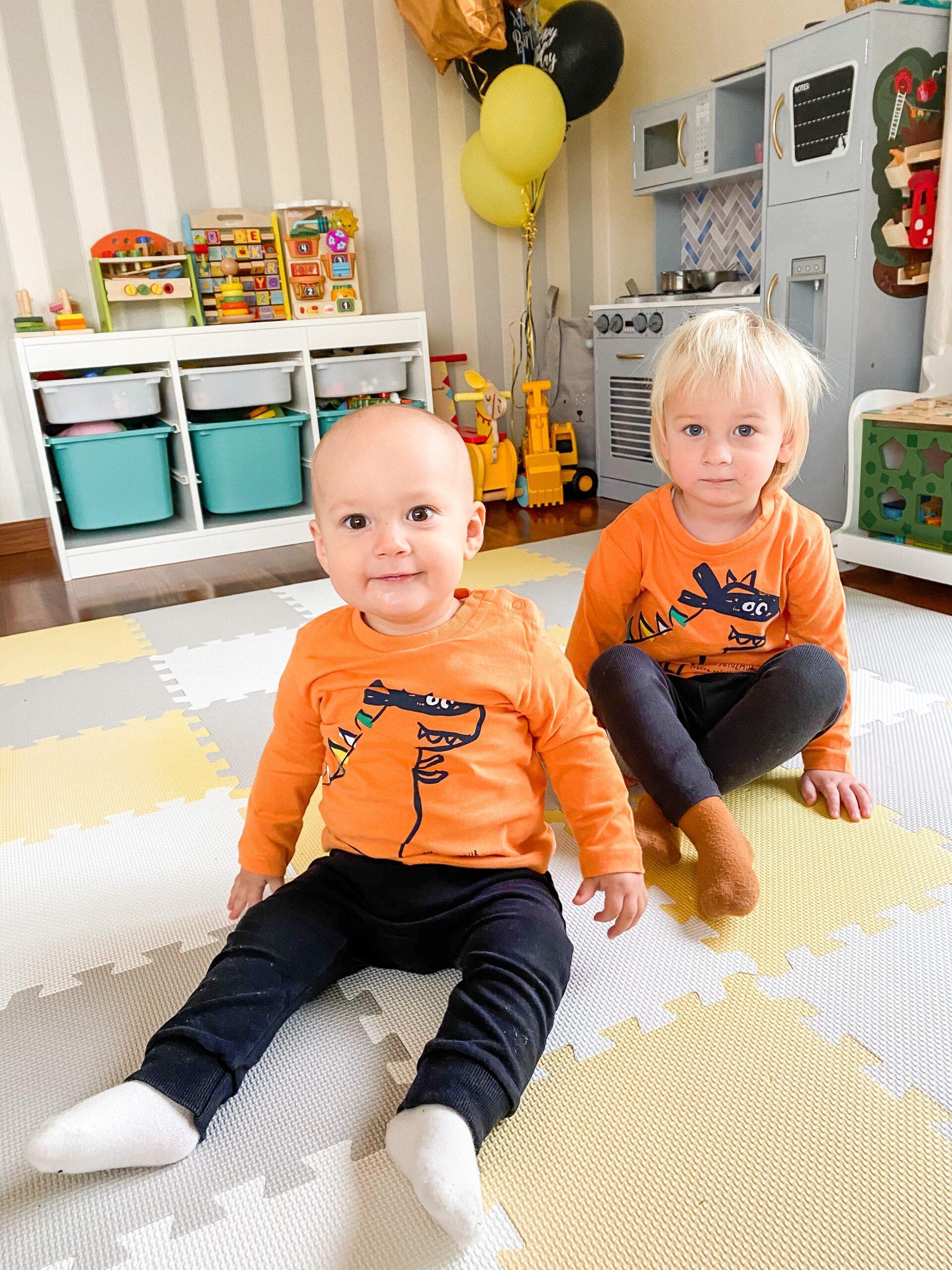 Dwaj mali chłopcy ubrani w takie same pomarańczowe koszulki.