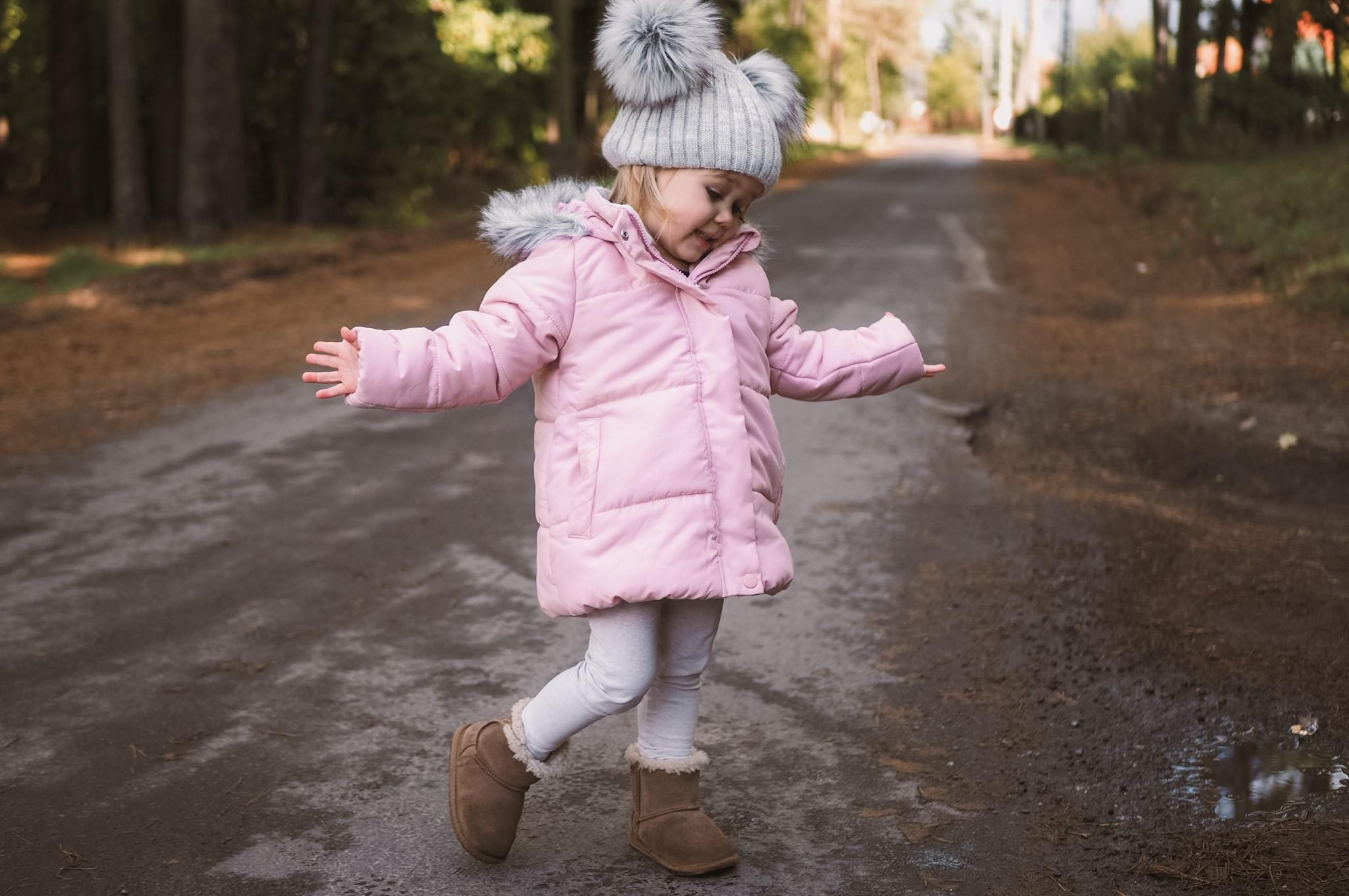 Dziewczynka w różowej kurtce stojąca na drodze w lesie.