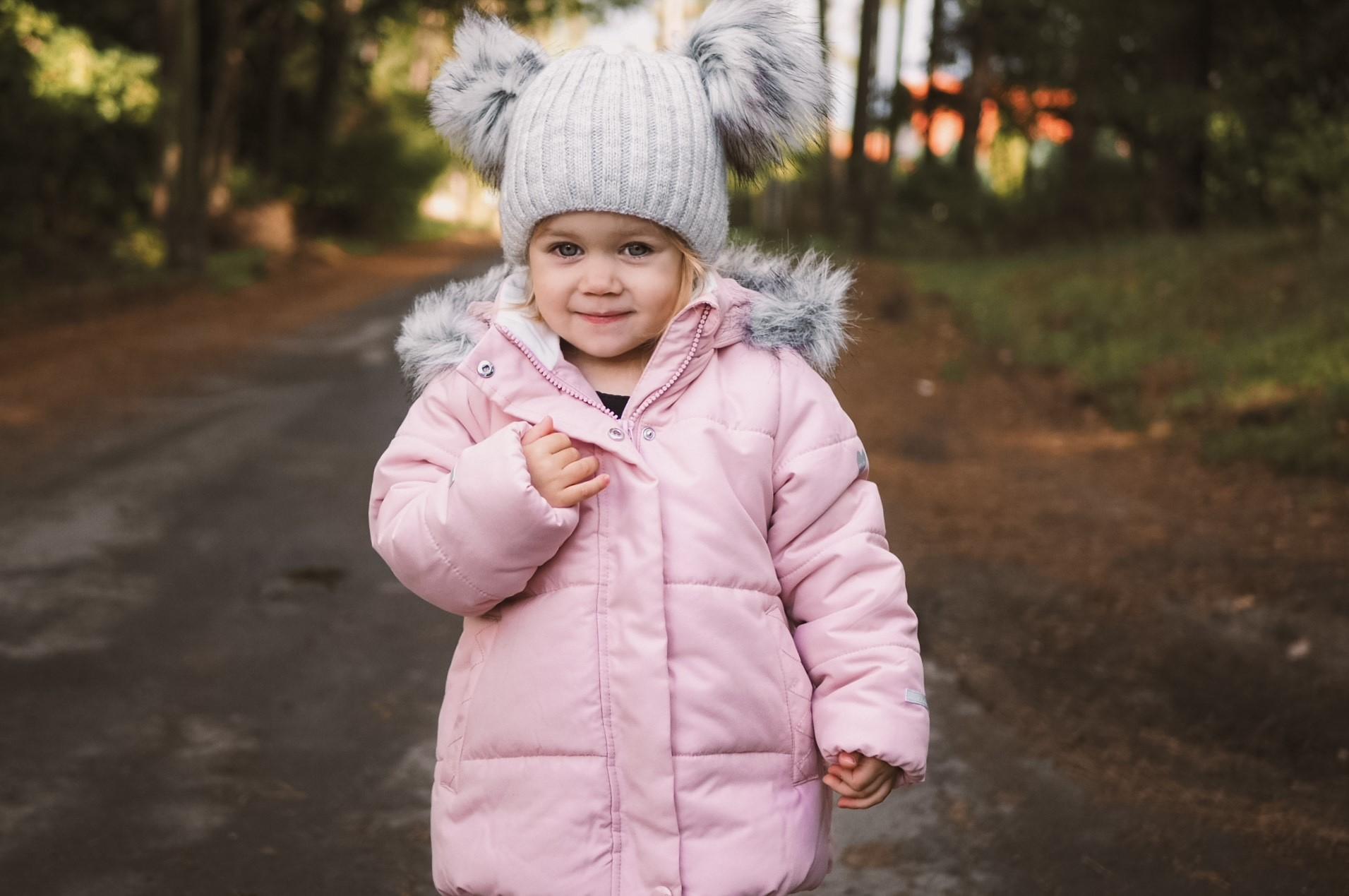 Mała dziewczynka w różowej kurtce i czapce na głowie.