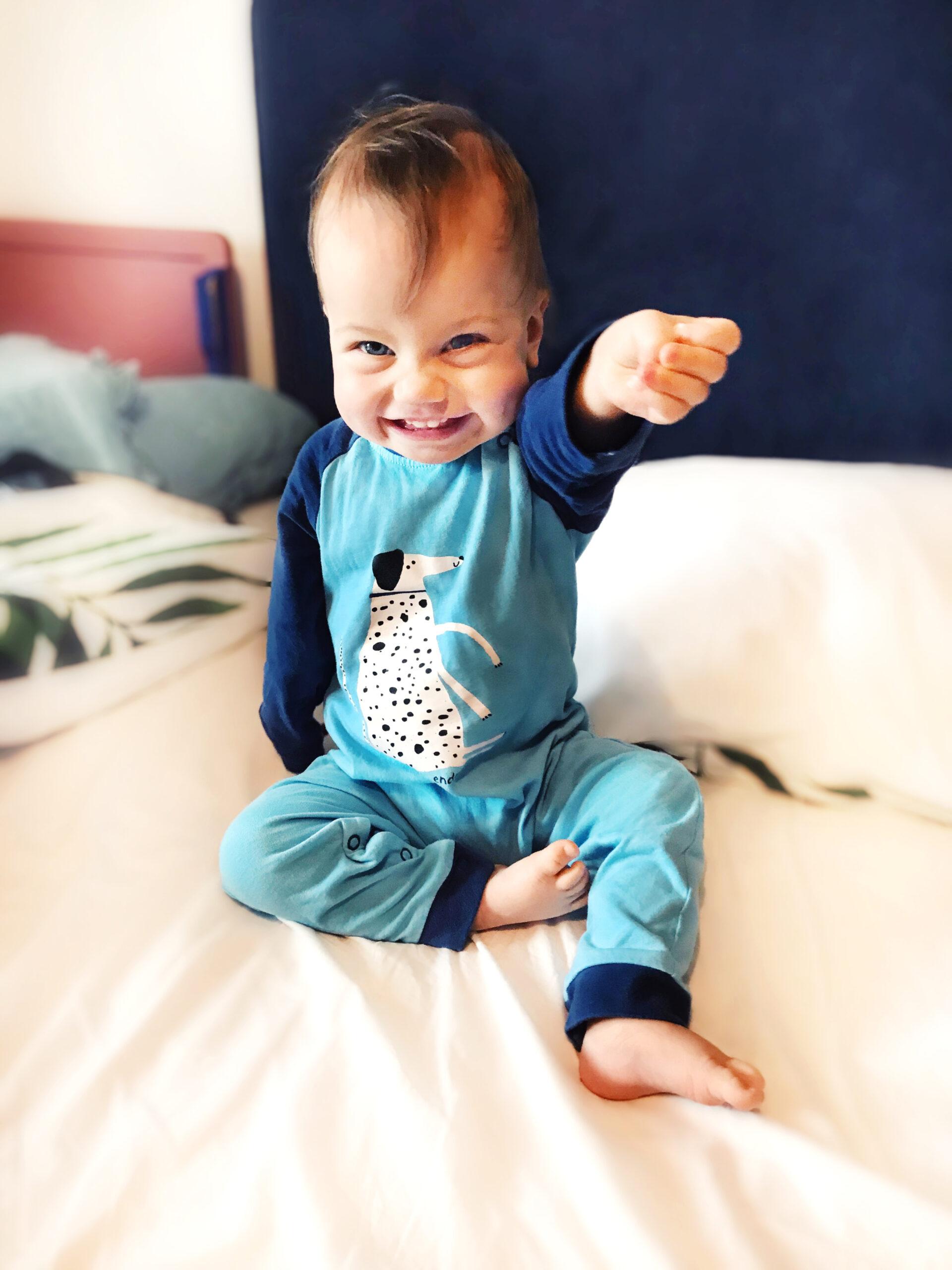 Siedzący niemowlak w niebieskim pajacyku z pieskiem.